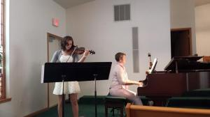 Kate playing the violin while Mother accompanies her.
